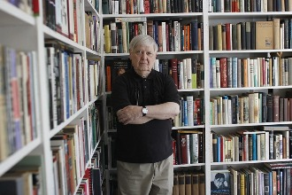 William Gass in his library The Mantle image